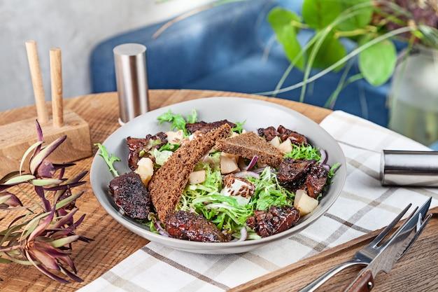 Zamyka w górę widoku na świeżej zdrowej sałatce. sałatka z sałatą, wątróbką drobiową, grzankami, czerwoną cebulą i serem. miska na lunch serwowana w restauracji. koncepcja zrównoważonej zdrowej żywności. talerz z przekąskami
