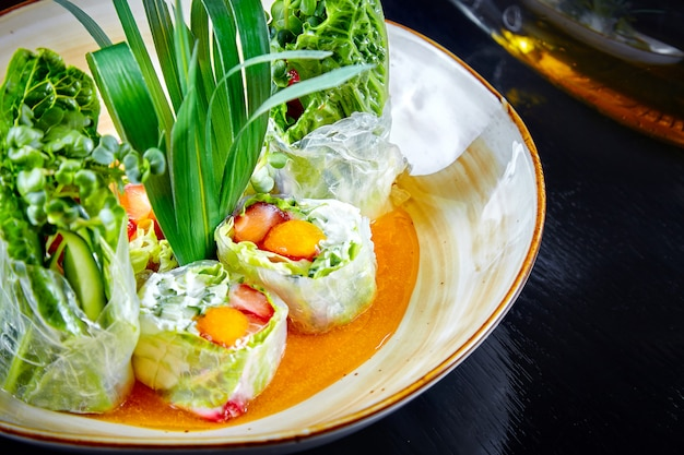 Zamyka w górę widoku na zielonej sajgonce z zieloną cebulą, krewetkami i śmietanką w pucharze. selektywne ustawianie ostrości. japońskie jedzenie. suchi roll. owoce morza. ryba na lunch. zdrowe, dietetyczne, zbilansowane jedzenie. papier ryżowy