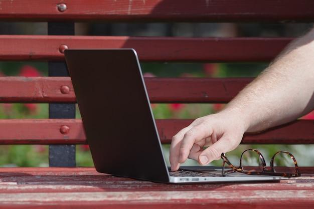 Zamyka w górę widoku otwarty laptop na ławce