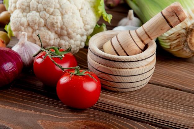 Zamyka w górę widoku pomidory i inni warzywa z czosnku gniotownikiem na drewnianym tle