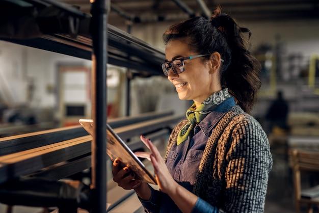 Zamyka w górę widoku pracowita skoncentrowana profesjonalista motywująca biznesowa kobieta trzyma pastylkę obok półki z metal drymbami w tkanina warsztacie.