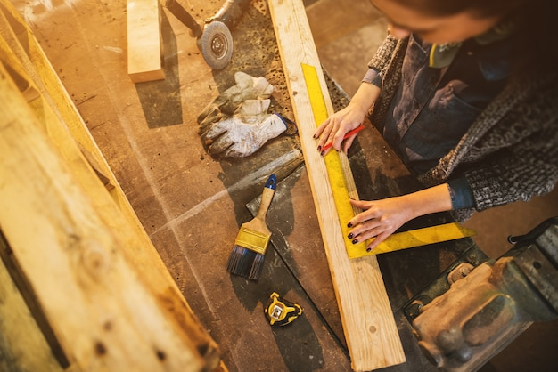 Zamyka w górę widoku pracowita skupiająca się fachowa poważna cieśla kobiety mienia władca i ołówek podczas gdy robić ocenom na drewnie przy stołem w tkanina warsztacie.
