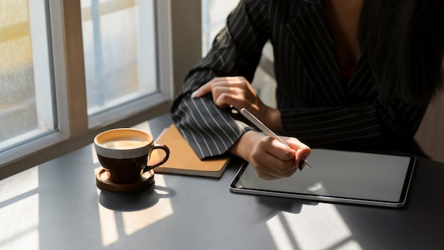 Zamyka w górę widoku pracuje na cyfrowej pastylce w sklep z kawą żeński freelancer