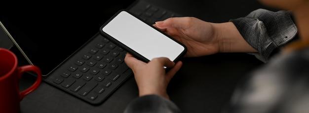 Zamyka w górę widoku pracuje z egzaminu próbnego smartphone i dostawami na czerń stole żeński przedsiębiorca