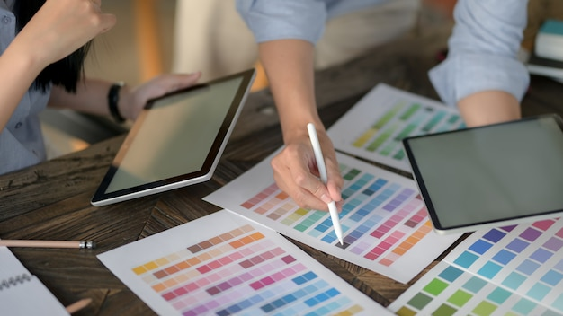 Zamyka w górę widoku projektant drużyna używa cyfrową pastylkę podczas gdy wybierający kolor na koloru swatch na rocznika drewnianym stole