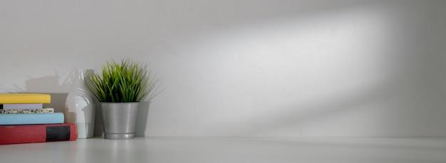 Zamyka w górę widoku prosty workspace z książkami, dekoracją i kopii przestrzenią na bielu stole