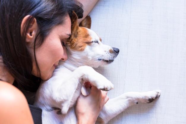 Zamyka w górę widoku psi lying on the beach na podłoga z jego właścicielem. kobieta z zamkniętymi oczami. styl życia w pomieszczeniu i koncepcja miłości do zwierząt