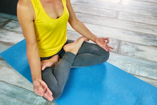 Zamyka w górę widoku robi ranek joga w domu kobieta, w lotosowej pozyci.