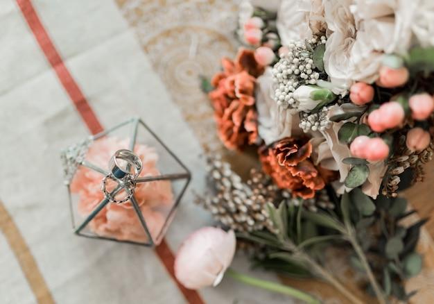 Zamyka w górę widoku różowi kwiaty, obrączki ślubne w wieśniaku boksuje na stole