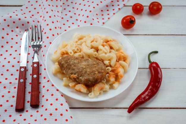 Zamyka w górę widoku surved na białym talerzu na drewnianym stole mięsny kotlet. bacground jest ozdobiony czerwoną papryką chili, widelcem, nożem i pomidorami.