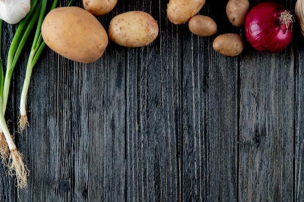 Zamyka w górę widoku warzywa jako kartoflany czerwonej cebuli scallion na drewnianym tle z kopii przestrzenią