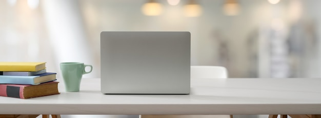 Zamyka w górę widoku wygodny stół roboczy z otwartym laptopu, książek, kubka i kopii przestrzenią na bielu stole
