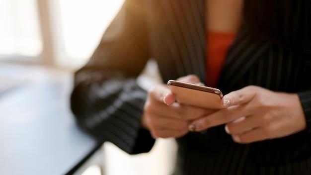 Zamyka w górę widoku żeński używa smartphone w wygodnym miejscu pracy