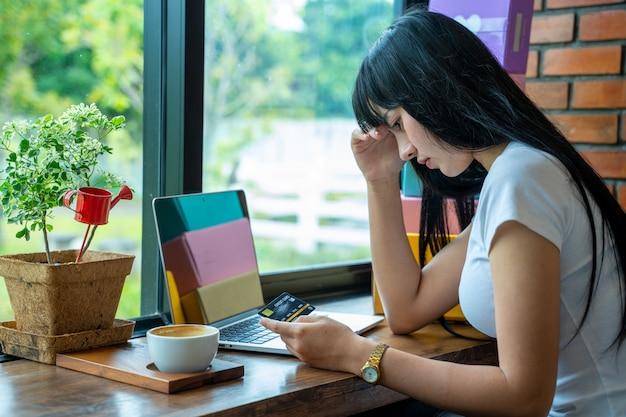 Zamyka w górę wizerunku azjatycka kobieta stresuje się z kartą kredytową, azjatycka kobieta próbuje znajdować pieniądze spłacać dług karty kredytowej.