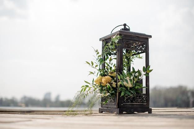 Zamyka w górę żelaznej latarni dekorującej tropikalnymi kwiatami jako ślubny wystrój na brzeg rzeki