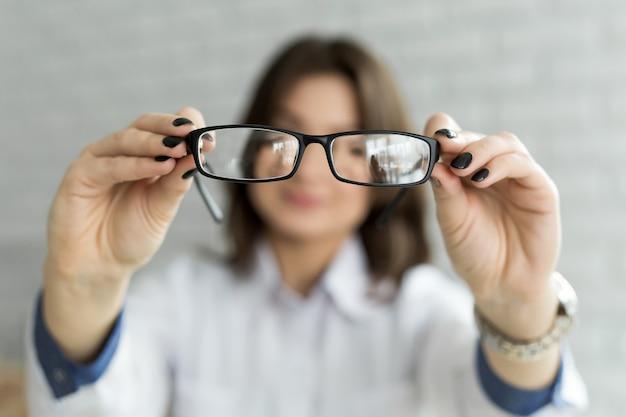 Zamyka w górę żeńskich ręk trzyma eyeglasses. koncepcja okulistyki