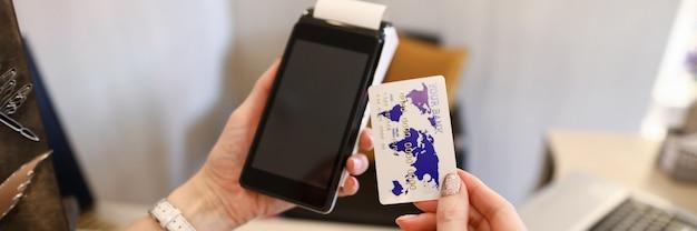 Zamyka w górę żeńskich ręk trzyma kredytowego czytnika kart