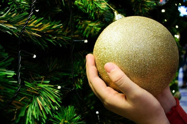 Zamyka w górę żeńskich ręk trzyma złotą piłkę. ozdobiona choinka w kolorze srebrnym