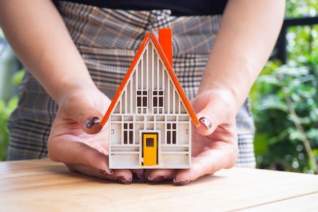 Zamyka w górę żeńskiego ręki mienia domu modela