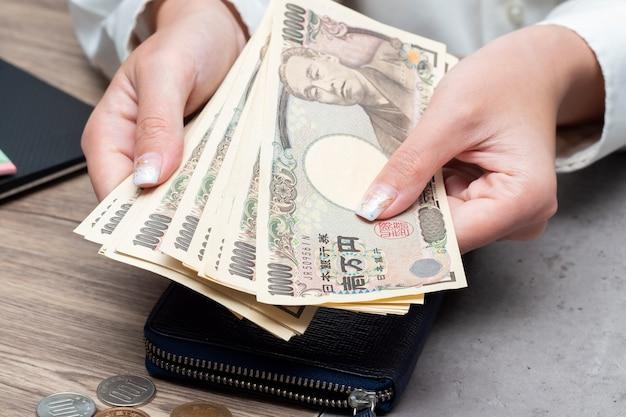 Zamyka w górę żeńskiej ręki trzyma japońskiego jena 10000 notatek