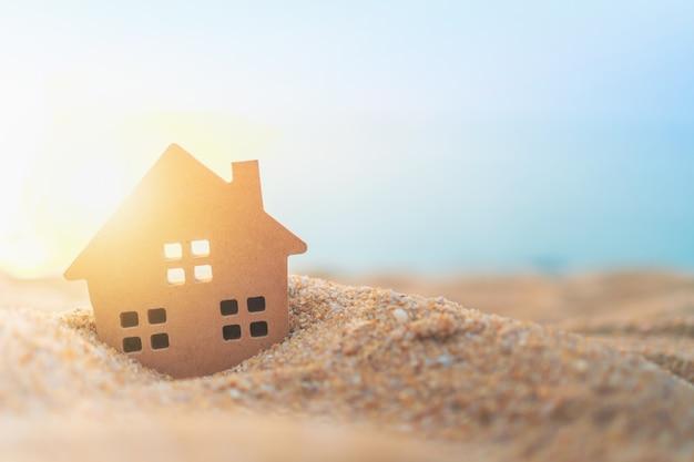 Zamykający w górę malutkiego domu modela na zielonej trawie z światło słoneczne ścianą.