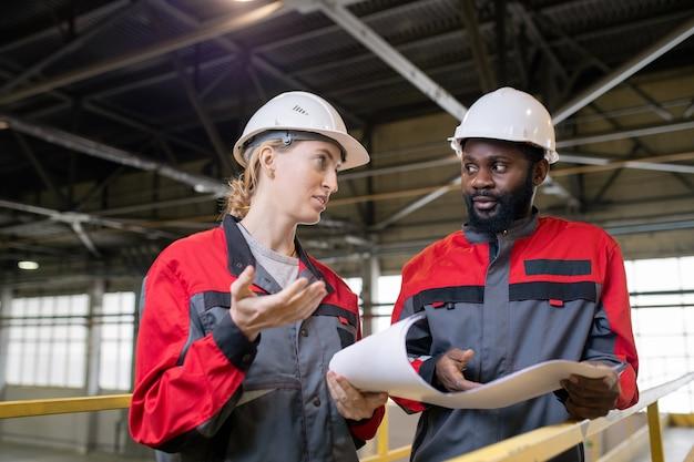 Zamyśleni młodzi, wieloetniczni pracownicy w kaskach dyskutują o planie budowy na budowie