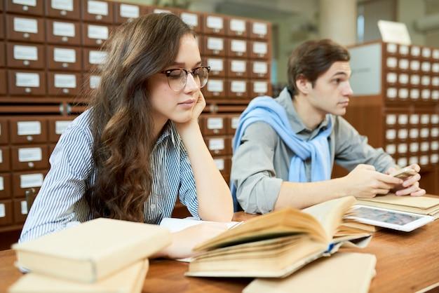 Zamyśleni studenci w bibliotece akademickiej