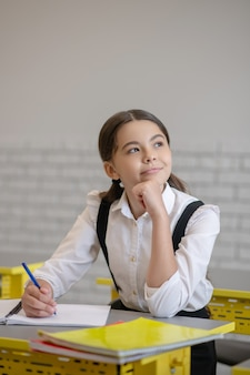 Zamyślenie. zamyślona uczennica z długimi ciemnymi włosami z piórem w dłoni przy biurku, patrząc na bok