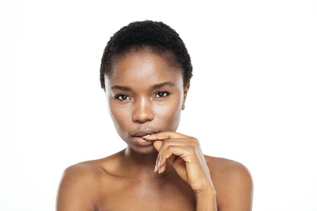 Zamyślona afroamerykańska kobieta patrząca na kamerę na białym tle