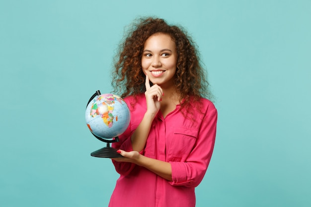 Zamyślona afrykańska dziewczyna w zwykłych ubraniach trzymaj w rękach globus ziemi, podnieś rękę podpierając się na brodzie na białym tle na niebieskim turkusowym tle. ludzie szczere emocje, koncepcja stylu życia. makieta miejsca na kopię.