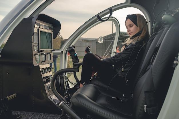 Zamyślona animatorka w czerni siedzi na siedzeniu drugiego pilota w helikopterze