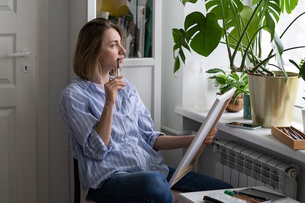 Zamyślona artystka maluje obraz na płótnie, w zamyśleniu wygląda przez okno w poszukiwaniu inspiracji