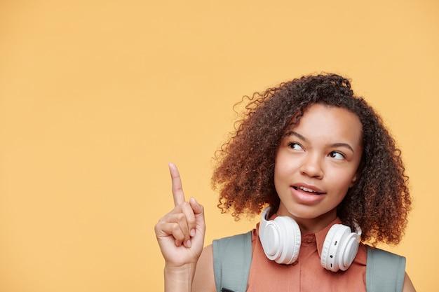 Zamyślona atrakcyjna czarna nastolatka z bezprzewodowymi słuchawkami na szyi skierowaną w górę, mając ciekawy pomysł, jasne tło