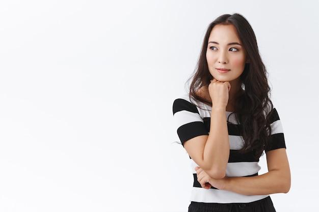 Zamyślona, atrakcyjna i zamyślona młoda azjatycka brunetka w pasiastym t-shircie, trzymająca rękę pod brodą, odwracająca wzrok marzycielska, uśmiechnięta kontemplująca kogoś przechodzącego, stojąca na białym tle