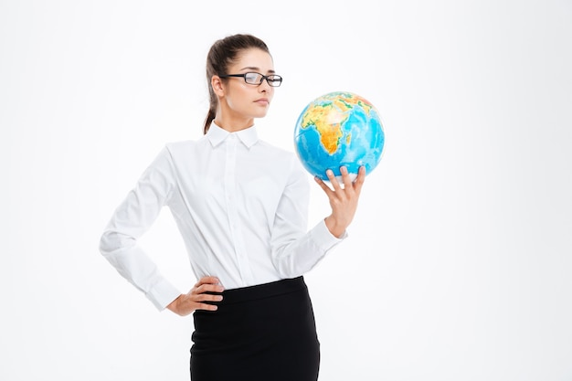 Zamyślona atrakcyjna młoda biznesowa kobieta trzyma kulę ziemską