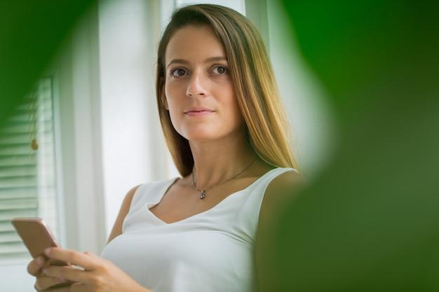 Zamyślona atrakcyjna młoda kobieta przy użyciu telefonu komórkowego