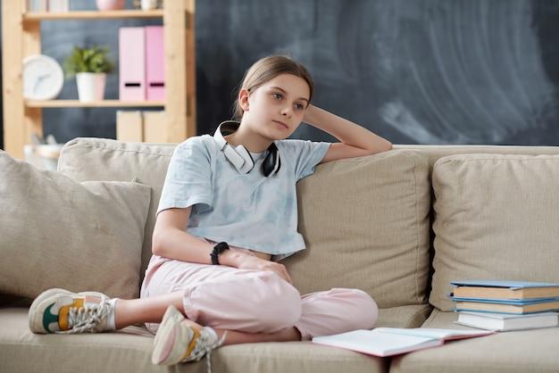 Zamyślona atrakcyjna nastolatka z bezprzewodowymi słuchawkami na szyi, siedząca na kanapie z podręcznikami