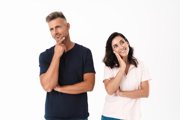 Zamyślona, atrakcyjna para w swobodnym stroju, stojąca na białym tle nad białą ścianą, odwracająca wzrok