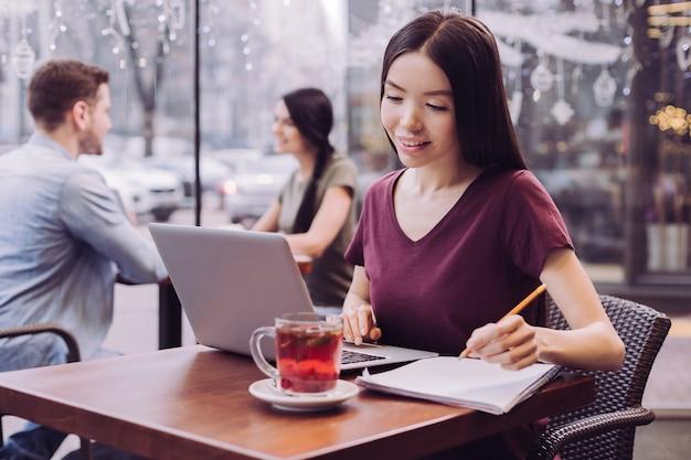 Zamyślona atrakcyjna studentka korzysta z laptopa, patrząc na ekran i zapisując informacje