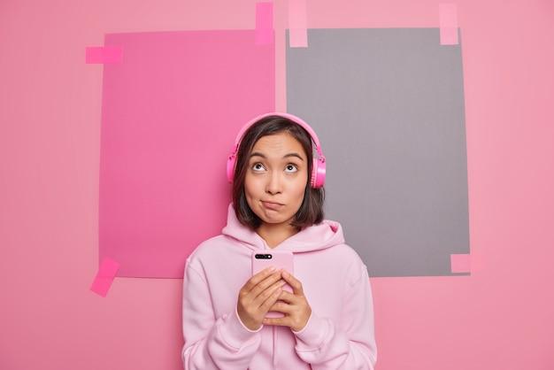 Zamyślona azjatka lubi nową aplikację na smartfonie do odtwarzania piosenek, słucha ulubionej muzyki skoncentrowanej powyżej, ma zamyślony wyraz twarzy, ubrana w pozy z kapturem na różowej ścianie, uważa coś
