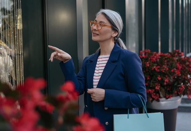 Zamyślona azjatycka dojrzała kobieta trzymająca torbę na zakupy wybierająca odzież w centrum handlowym koncepcja sprzedaży