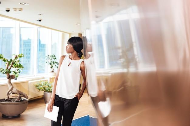 Zamyślona bizneswoman opierając się o ścianę w biurze