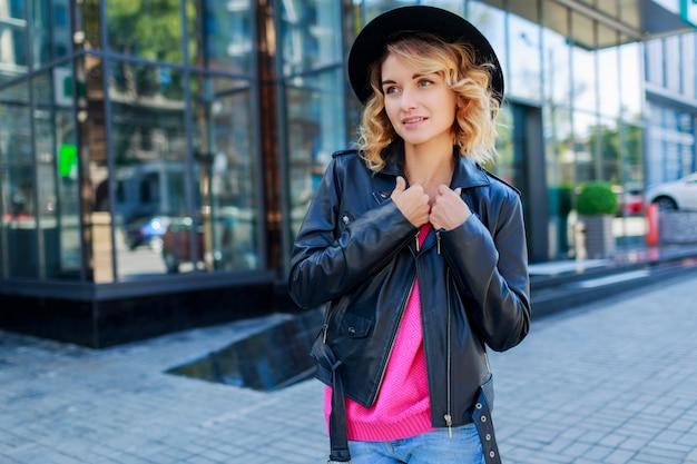 Zamyślona blond krótkowłosa kobieta spacerująca po ulicach dużego nowoczesnego miasta. modny strój miejski. niezwykłe różowe okulary przeciwsłoneczne.