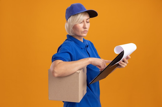 Zamyślona blondynka dostarczająca kobieta w niebieskim mundurze i czapce stoi w widoku z profilu trzymając karton pod pachą i schowek patrząc na schowek kładąc na nim palec