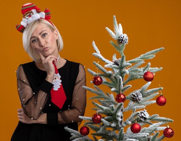 Zamyślona blondynka w średnim wieku nosząca opaskę i krawat świętego mikołaja stojąca obok udekorowanej choinki dotykająca policzka palcem patrząca na pomarańczową ścianę