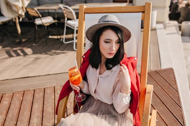 Zamyślona brunetka kobieta odwracając wzrok podczas odpoczynku w fotelu w słoneczny dzień