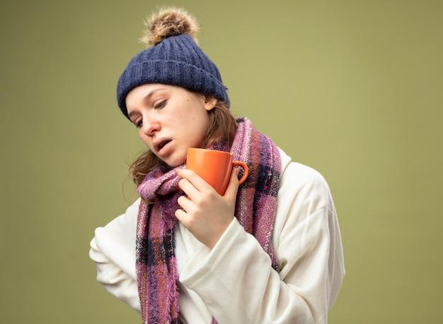 Zamyślona chora dziewczyna szuka puchowej białej szaty i czapki zimowej z szalikiem, trzymając filiżankę herbaty na białym tle na oliwkową zieleń