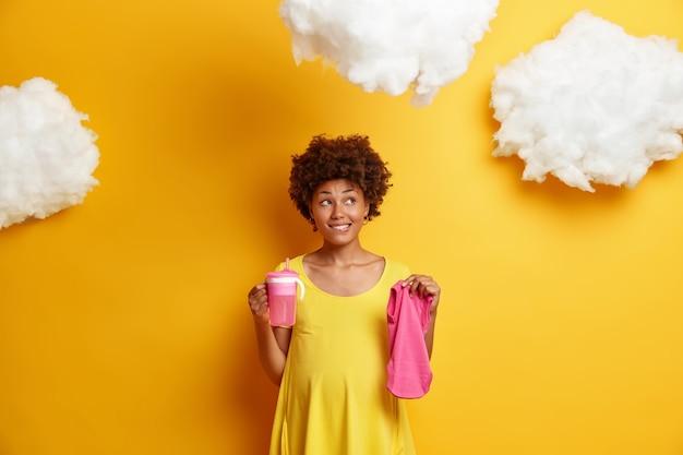 Zamyślona ciężarna młoda afroamerykańska kobieta marzy o dziecku i przyszłym życiu trzyma butelkę do karmienia i ubranka dziecięce gryzie usta w zamyśleniu pozuje