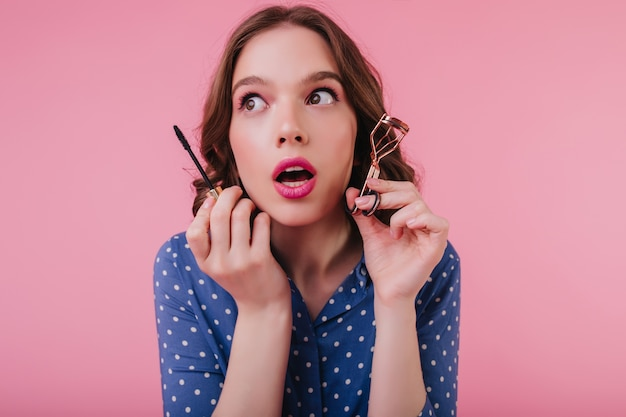 Zamyślona czarująca młoda kobieta trzyma tusz do rzęs i odwraca wzrok z otwartymi ustami. modna dziewczyna podkręca rzęsy przed datą.