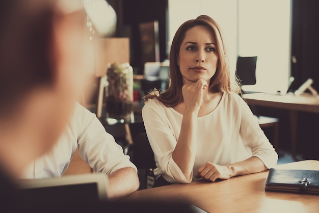 Zamyślona czerwona z włosami kobieta siedzi na rozmowie
